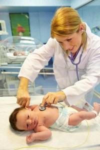 Pediatra explorando a bebe recién nacido